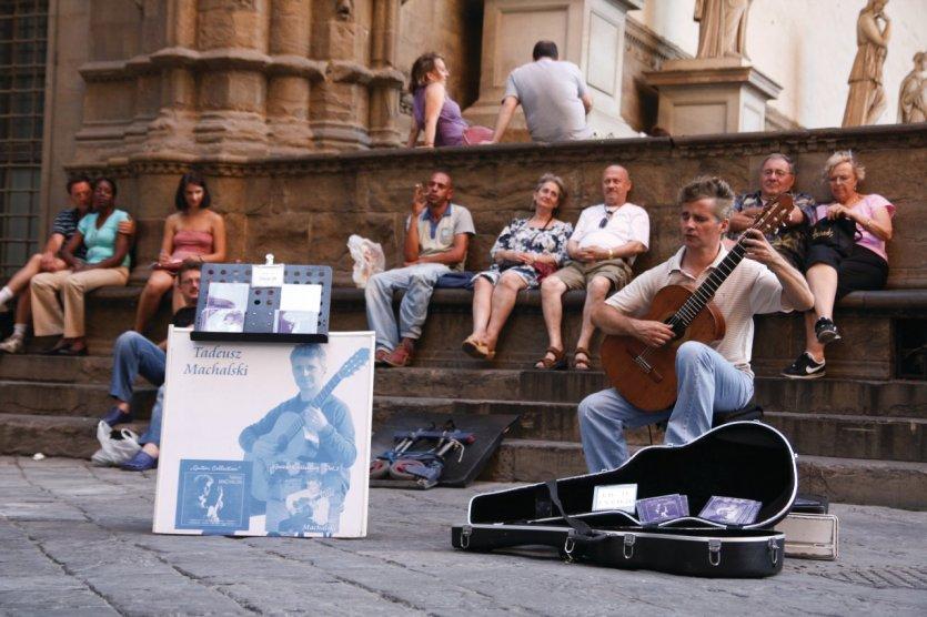 Jeune guitariste offrant sa musique aux touristes de passage.