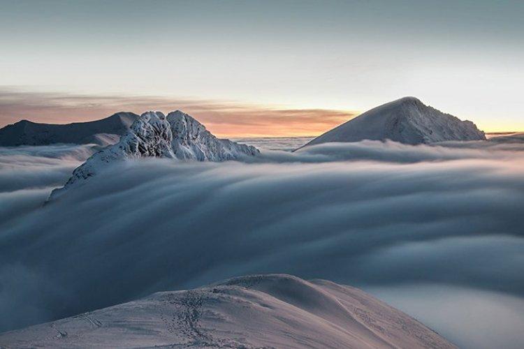 Nuages débordants les sommets de montagnes - © Getty Images