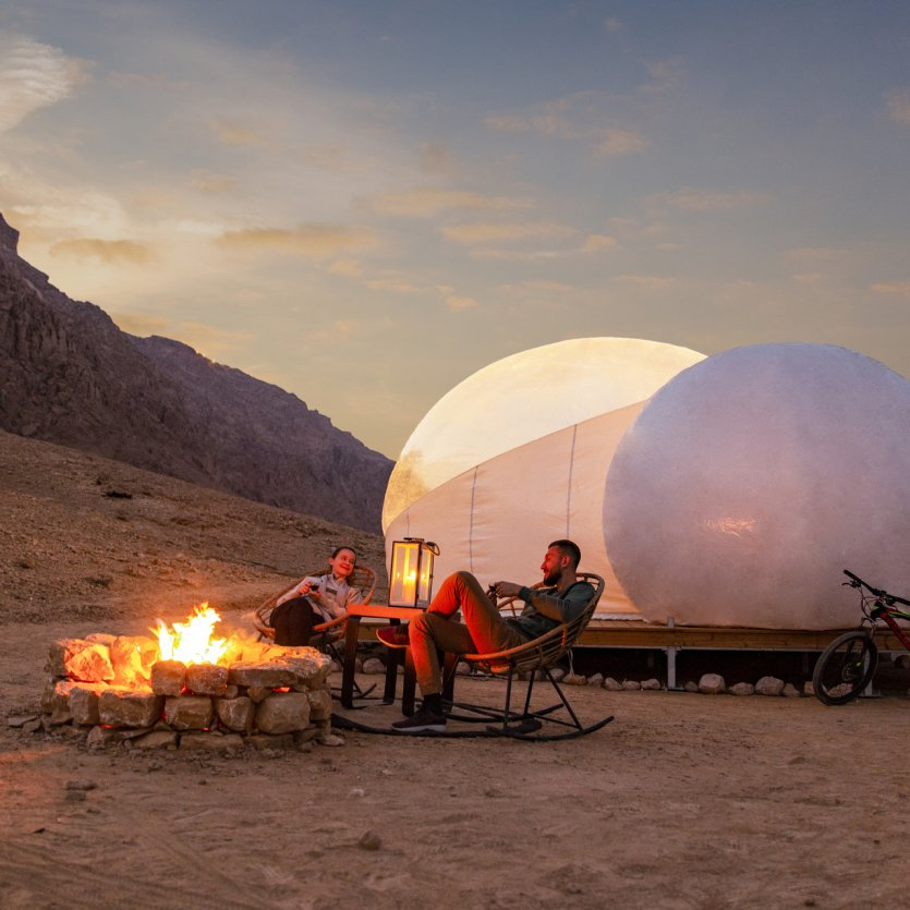 1. Jebel Hafit Desert Park. Au Sud du pays, à la frontière avec le Sultanat d'Oman, se trouve la montagne du Jebel Hafit qui abrite sur ses pentes des sites archéologiques vieux de plus de 5000 ans, classés au patrimoine mondial de l'UNESCO. Ouvert cette année, la zone protégée du Jebel Hafit Desert Park permet de profiter des paysages extraordinaires de la région, entre wadis et roches escarpées, nichées entre montagne, désert et palmeraie. Les visiteurs peuvent maintenant y passer la nuit en choisissant parmi différentes options de camping, de la tente bédouine traditionnelle aux bulles de glamping idéales pour profiter du ciel étoilé. La journée, les voyageurs peuvent partir en randonnée, s'essayer au vélo-cross, explorer la région à cheval ou remonter le temps en découvrant des tombes préservées datant du Néolithique. - © visitabudhabi