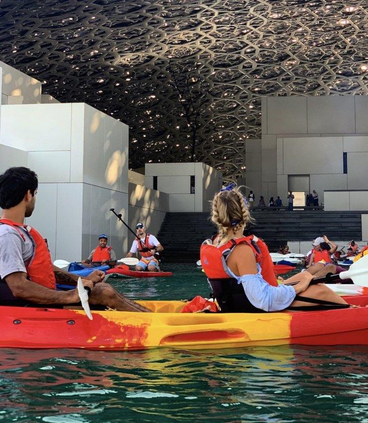 2.Découvrir le Louvre Abu Dhabi autrement : kayak et yoga sous le dôme. Depuis l'année dernière, le Louvre Abu Dhabi se découvre aussi depuis la mer : au petit matin ou au coucher du soleil, les visiteurs peuvent prendre place dans un kayak et partir sur l'eau à la découverte de l'architecture du musée signé Jean Nouvel. Semblant « posé » sur l'eau, le musée laisse la mer pénétrer sous le dôme principal à plusieurs endroits, donnant ainsi lieu à une visite des plus insolite du Louvre des sables. Une fois la balade en mer terminée, les visiteurs peuvent aller profiter des collections extraordinaires du musée ou bien se restaurer au Fouquet's Abu Dhabi.  L'esplanade sous le dôme, point central du musée baigné par la fameuse « pluie de lumière » crée par Jean Nouvel, sera aussi le théâtre à partir de 2021 de cours de yoga. - © visitabudhabi
