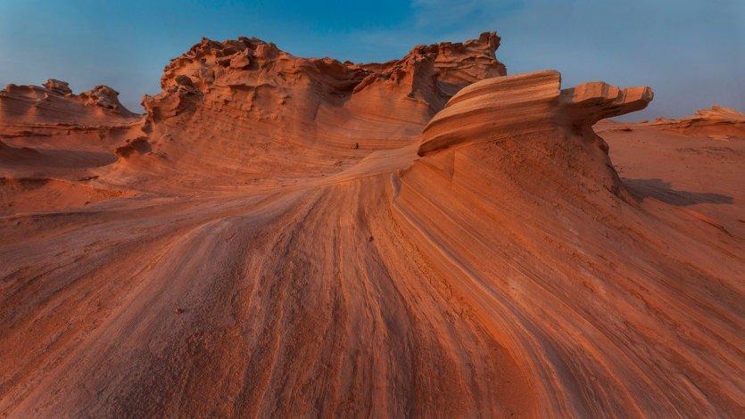 6.S'émerveiller devant les dunes fossiles d'Al Wathba Le désert du Rub al Khali, ou « quart vide », constitue la plus vaste étendue de sable ininterrompue au monde. Il est aussi au cœur de la culture et de l'histoire d'Abu Dhabi, témoin de traditions intemporelles comme la fauconnerie ou l'élevage de chameaux. Véritable paysage de dunes ocres se déployant à l'infini, le désert d'Abu Dhabi se caractérise par son relief, certaines de ses dunes comme celle de Tel Moreeb dépassant les 300 mètres de haut. Mais pour découvrir une véritable curiosité naturelle, il faut se rendre dans la portion de désert autour d'Al Wathba. Différant du sable meuble et des courbes changeantes de la crête des dunes, le désert d'Abu Dhabi abrite aussi des formations de sables durcies, érodées et façonnées petit à petit par les vents. Les dunes fossiles d'Al Wathba se présentent ainsi comme un champ de figures fossilisées aux formes uniques et étonnantes, qui peuvent rappeler par certains côtés le sud-ouest américain.  Pour profiter d - © visitabudhabi