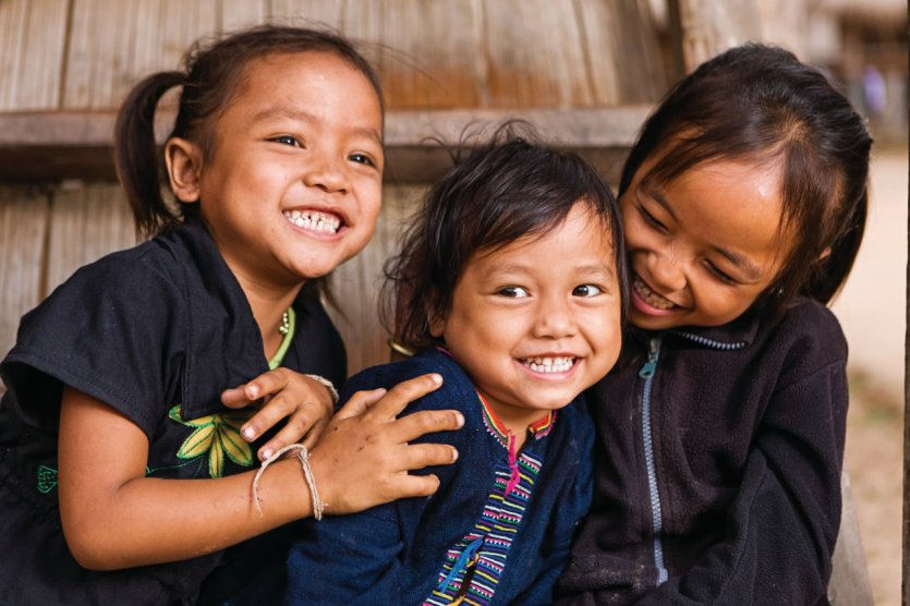 Three little girls having fun in the village in Northern Laos.