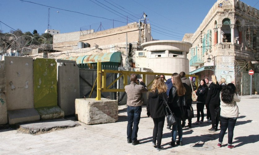 Membres d'Alternative Tourism Groupe devant une route bloquée par Israël.