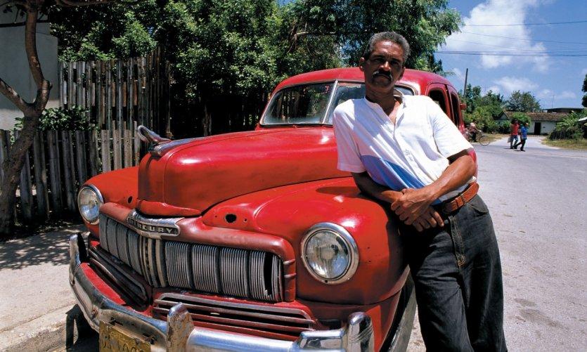 Cubain posant fièrement devant sa voiture.