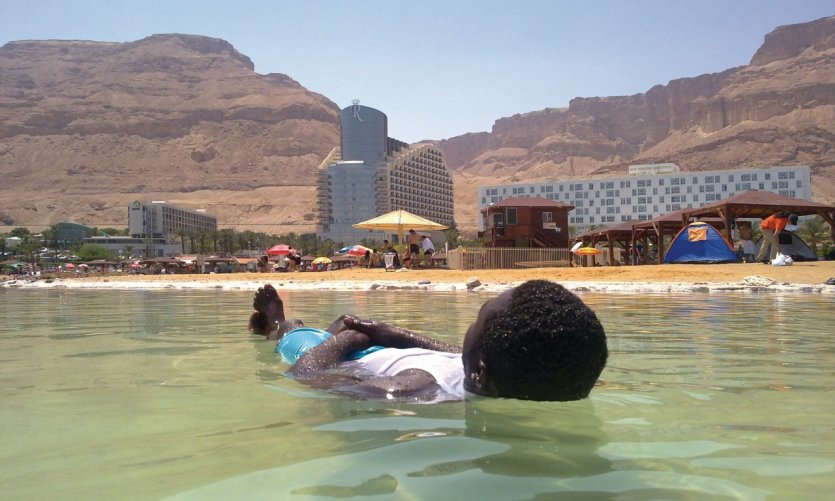Bain dans la mer Morte avec vue sur les resorts de Massada.