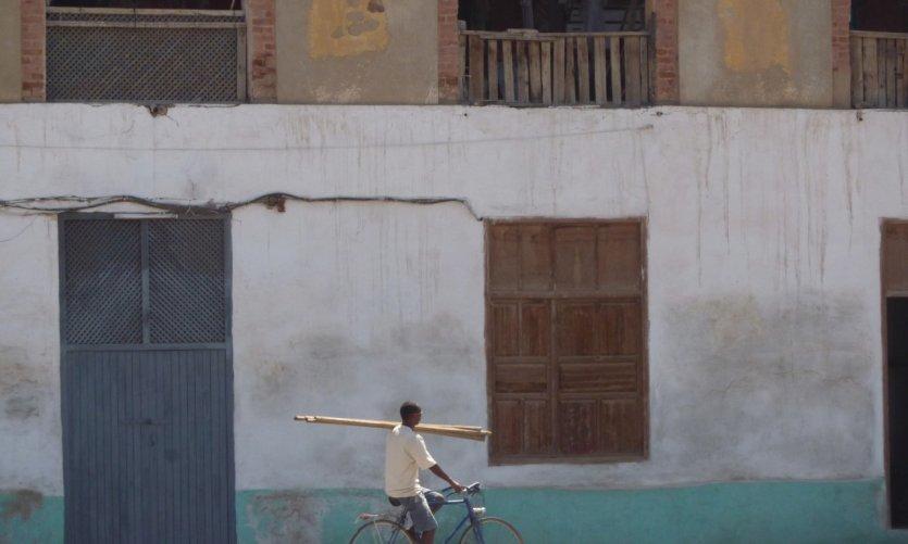 Sous le soleil de midi, un homme à bicyclette livre des planches sur un chantier du port.
