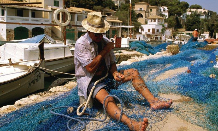 Pêcheur travaillant ses filets à Cala Figuera.
