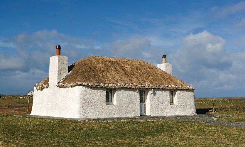 Traditionnelle maison de campagne blanchie couverte de chaume.