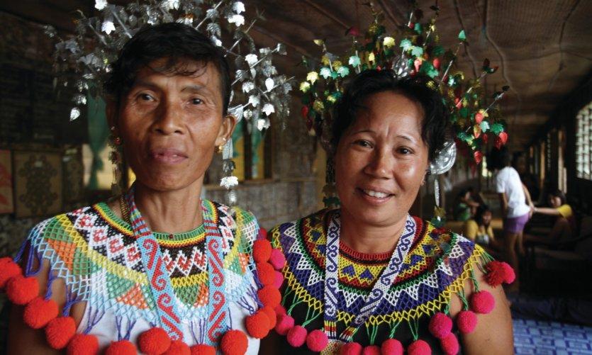 Femmes iban en costume traditionnel dans une longhouse