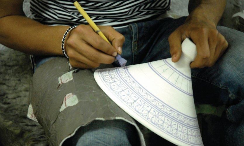 Artisan potier réalisant de la peinture sur céramique.