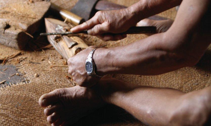 Sculpteur sur bois dans une longhouse