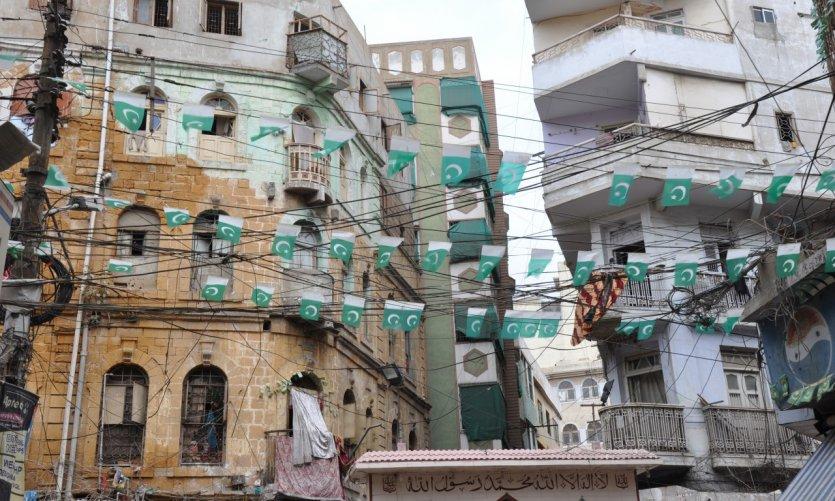 Drapeaux pakistanais et fils électriques s'entremêlent dans un quartier de Karachi.