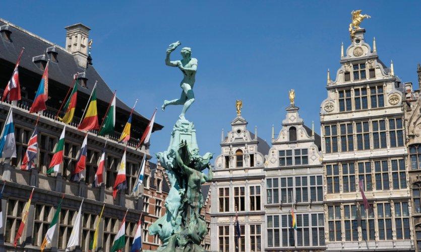 Statue de Silvius Brabo entourée par l'Hôtel de Ville et les maisons de guildes bordant la Grand-Place.