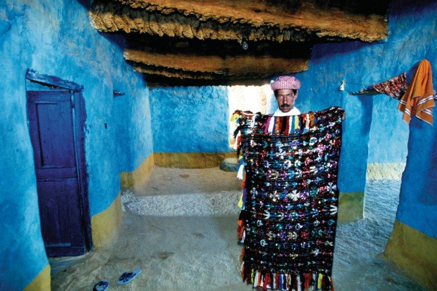 Maison typique avec un homme montrant un quilt bédouin. (© Sylvain GRANDADAM))