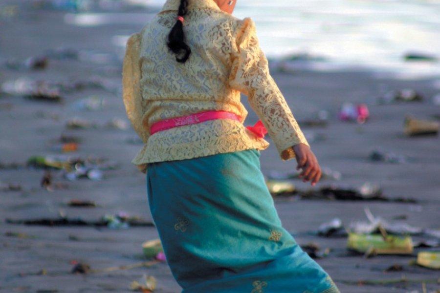 Détente sur la plage de Kuta pour cette fillette en costume traditionnel. (© Eloïse BOLLACK))