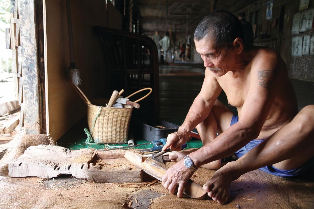Sculpteur sur bois dans une longhouse (© Stéphan SZEREMETA))