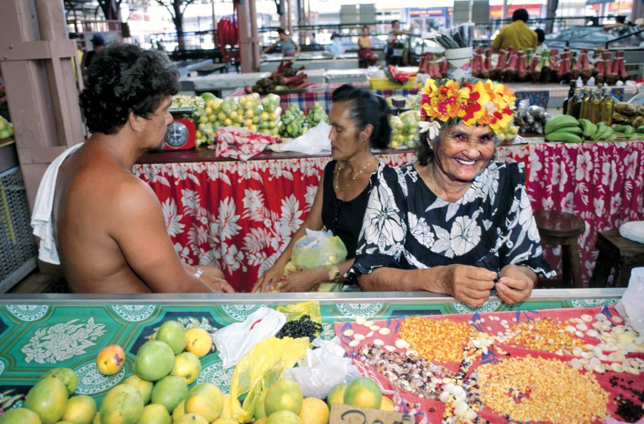 Une  Mama Ruau  fabrique des colliers de coquillages au marché de Papeete. (© Sylvain GRANDADAM))